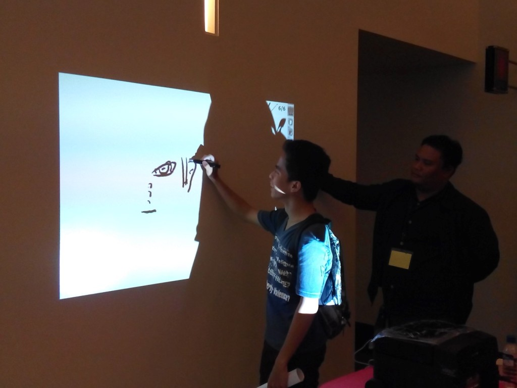 Francis Cuevas guiding a student on how to use the Interactive Whiteboard of K-Yan.